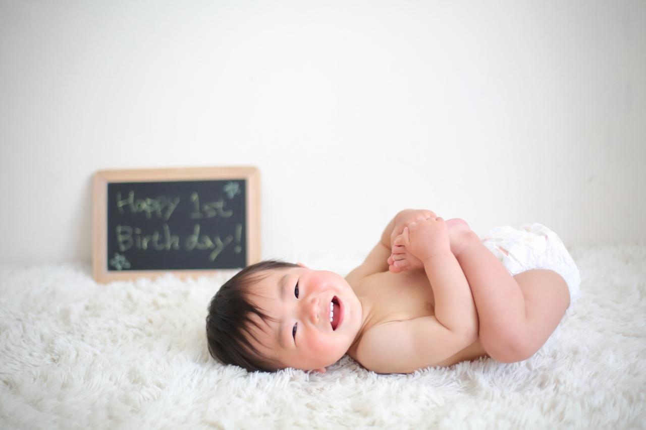 1歳男の子の誕生日記念撮影。オムツ姿でにっこり笑顔。