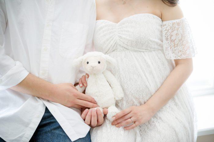 白ドレスでマタニティフォト。赤ちゃんのためのぬいぐるみと