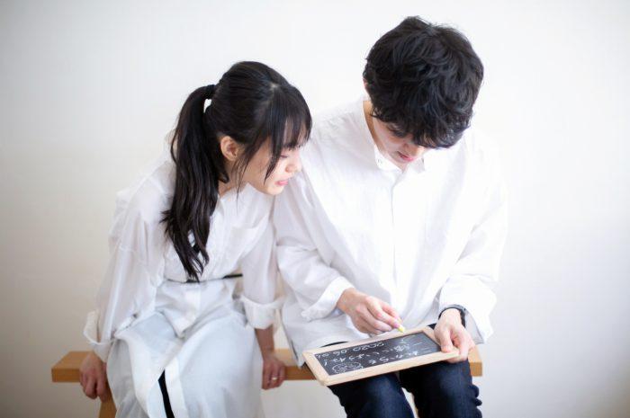 美男美女のカップル撮影。仲良しカップル。黒板にお互いへのメッセージ。なんて書いてくれてるのかな?