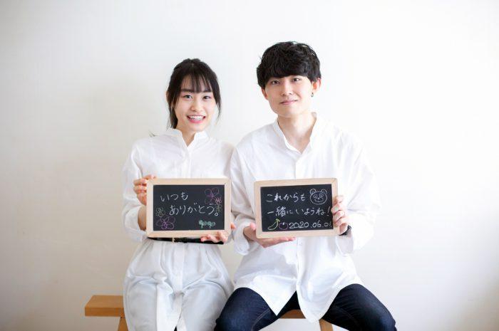 美男美女のカップル撮影。仲良しカップル。黒板にお互いへのメッセージ