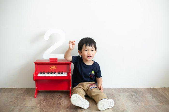 2歳男の子と一緒の家族撮影。親子リンクコーデが素敵です。赤いピアノの小物を気に入ってくれました。