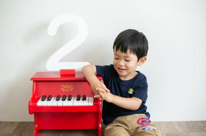 2歳男の子と一緒の家族撮影。親子リンクコーデが素敵です。赤いピアノの小物