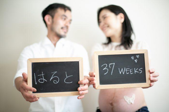37週のマタニティフォト,白のリンクコーデが素敵,真ん丸なお腹,黒板にメッセージを書いて